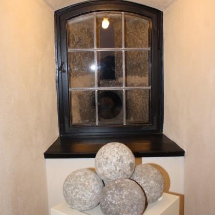 In der Wächterstube liegen vor dem Schießschartenfenster steinerne Kanonenkugeln aus Belagerungen im Mittelalter (Foto: Hans Eibauer)