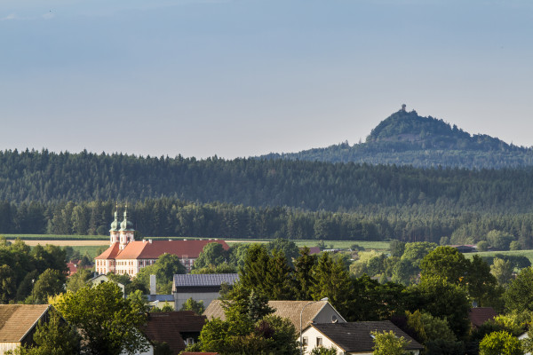 Blick auf das Kloster Speinshart, im Hintergrund der Rauhe Kulm (Foto: Tourismuszentrum Oberpfälzer Wald - Lkr. NEW)